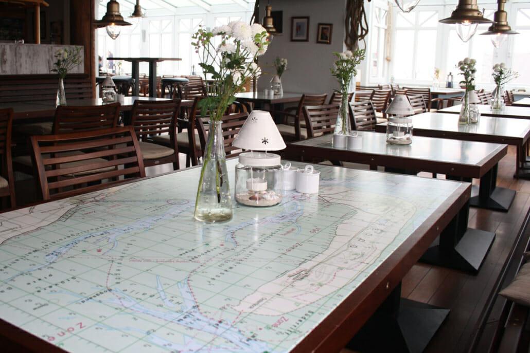 Nahaufnahme Tisch im Restaurant mit aufgedruckter Seekarte
