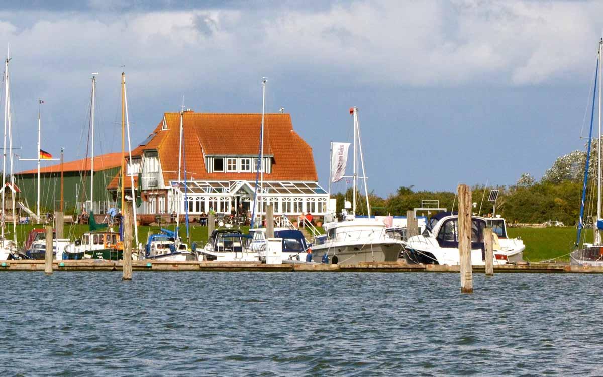 Yachthafen von Langeoog mit Booten und einem Deich mit Restaurant