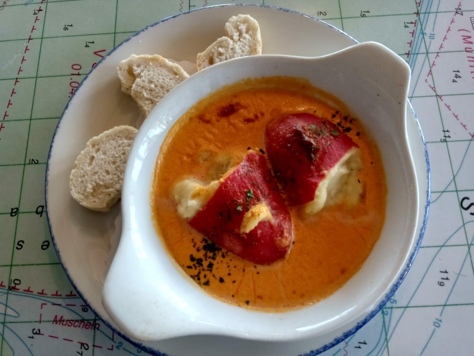 Schüssel auf einem Tisch mit Baguette, und zwei Peperonis in der Suppe
