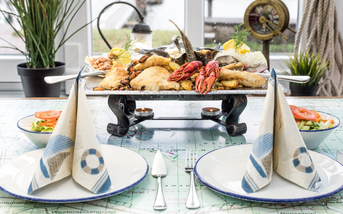 Gedeckter Tisch mit Fischplatte auf Rechaud